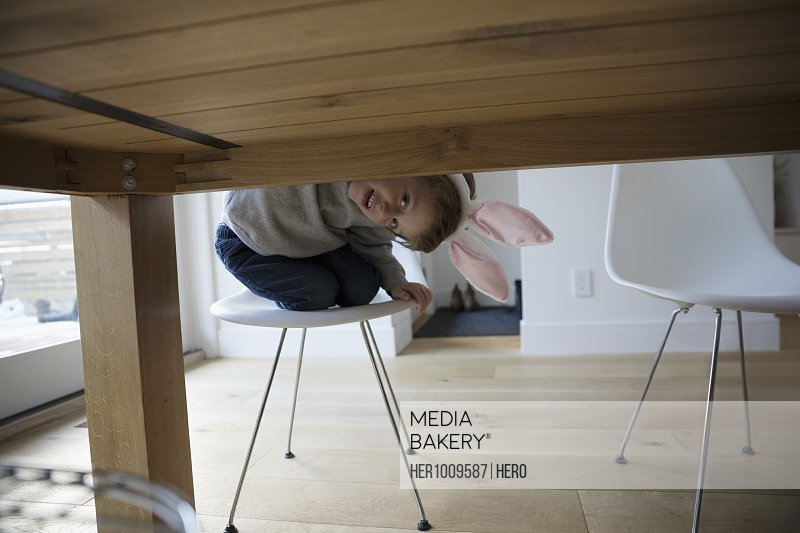 Portrait playful, cute boy in costume rabbit ears peering under dining table