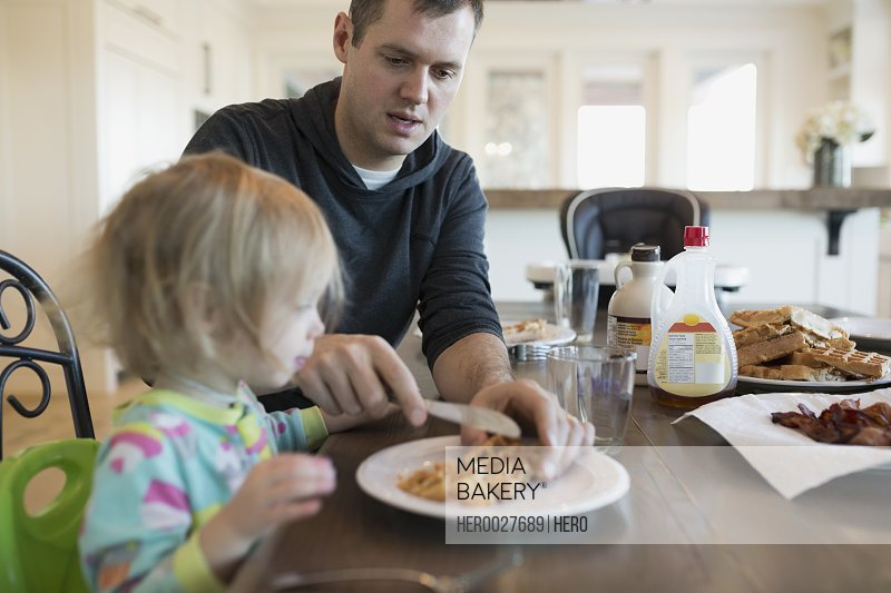 Father cutting waffles for daughter at breakfast table