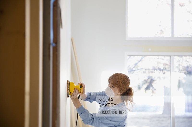 Woman wearing mask sanding wall in home