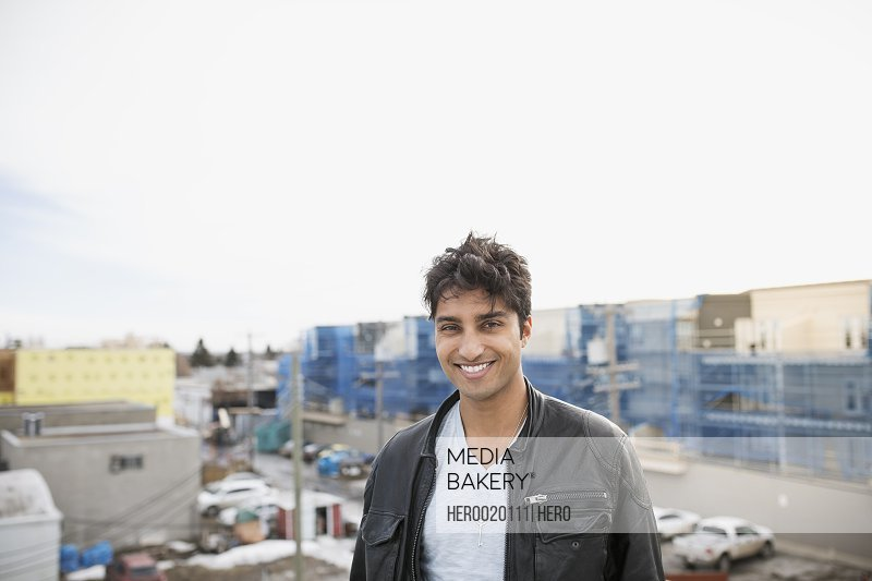 Portrait of smiling man on urban rooftop