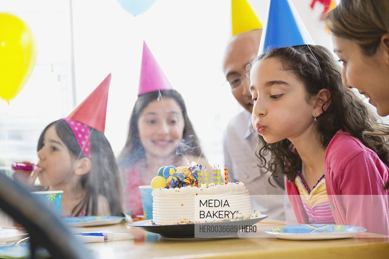 Little girl blowing out candles at birthday party