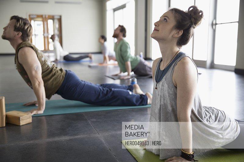 Smiling woman practicing yoga upward facing dog pose in yoga class studio