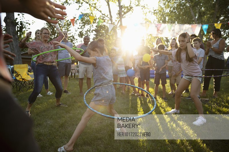 Neighbors spinning in plastic hoops at summer neighborhood block party in sunny park