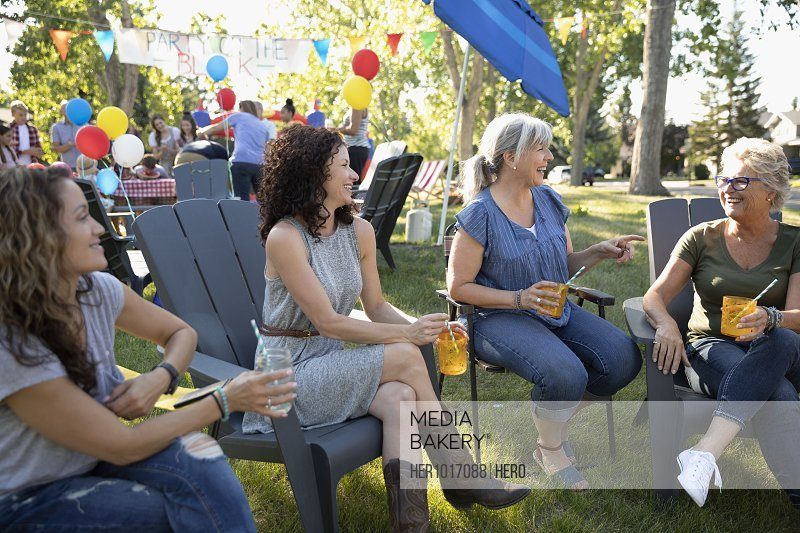 Female neighbors talking and drinking at summer neighborhood block party in park