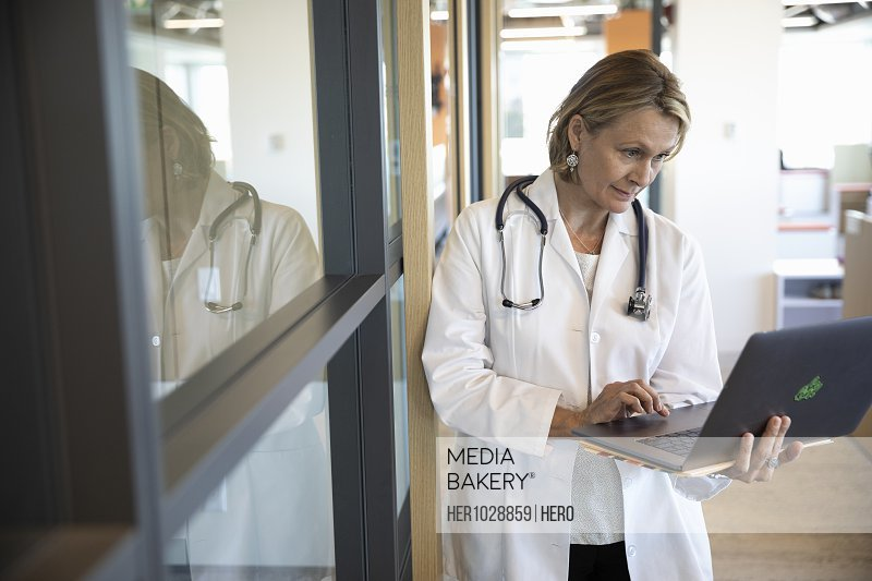 Female medical consultant standing and using laptop