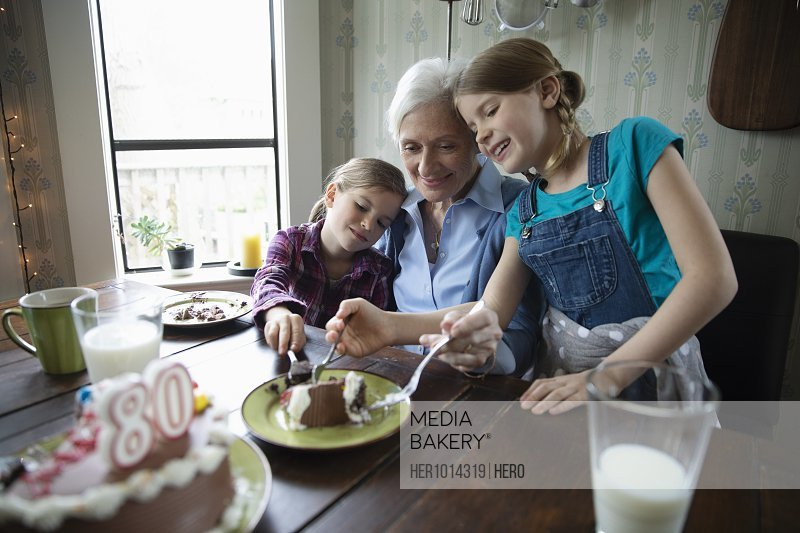 Grandmother and granddaughters celebrating birthday, sharing cake