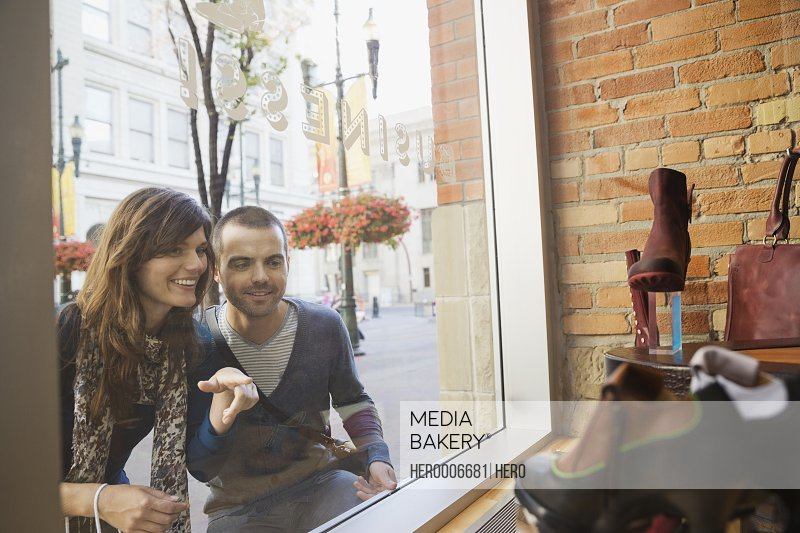 Smiling couple window shopping