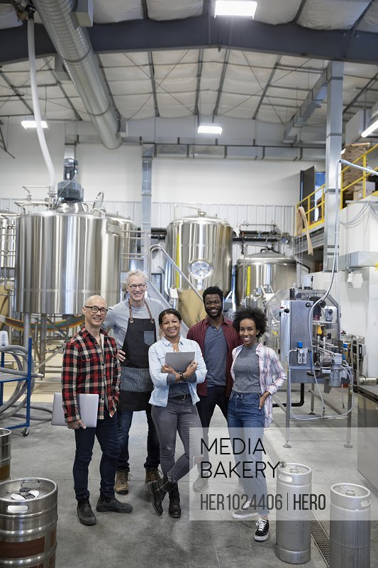 Portrait confident brewers working in brewhouse distillery