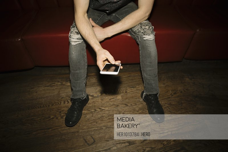 Male millennial using smart phone in nightclub