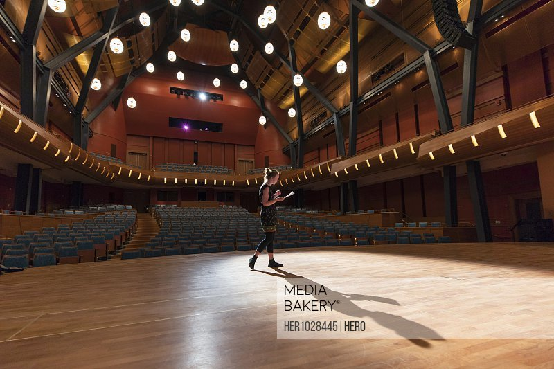 Female performer reviewing notes on stage in empty auditorium