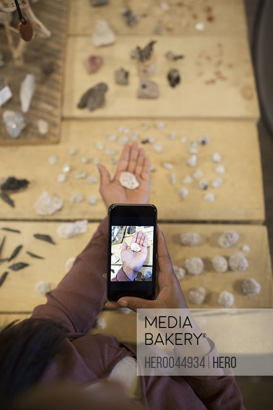 Overhead view female shopper photographing stone with camera phone in new age shop