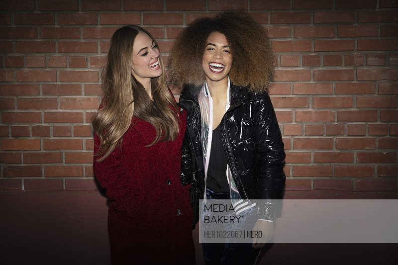 Portrait laughing young women friends standing at brick wall