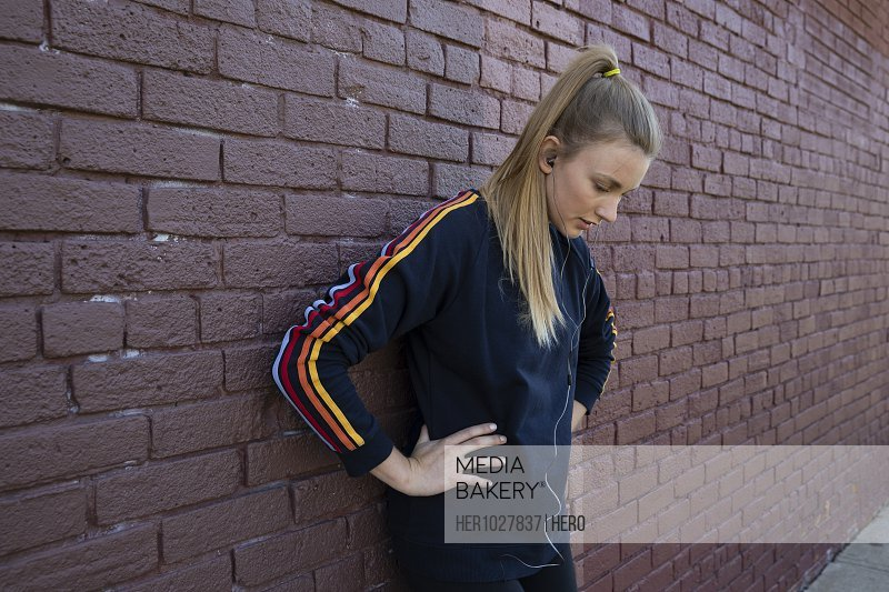 Young female runner resting against brick wall