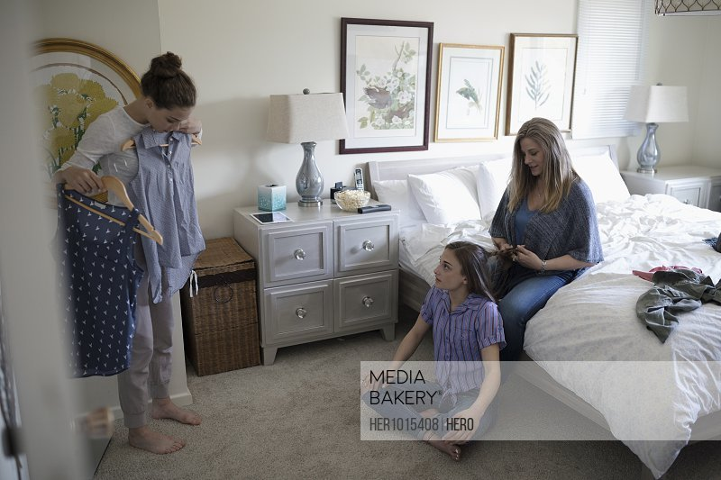 Mother helping teenage daughters with hair and clothing in bedroom