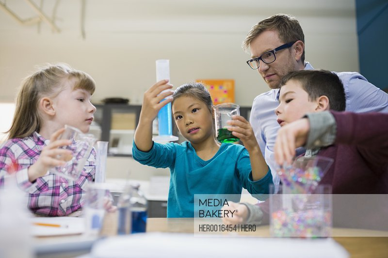 Teacher and elementary students conducting scientific experiment
