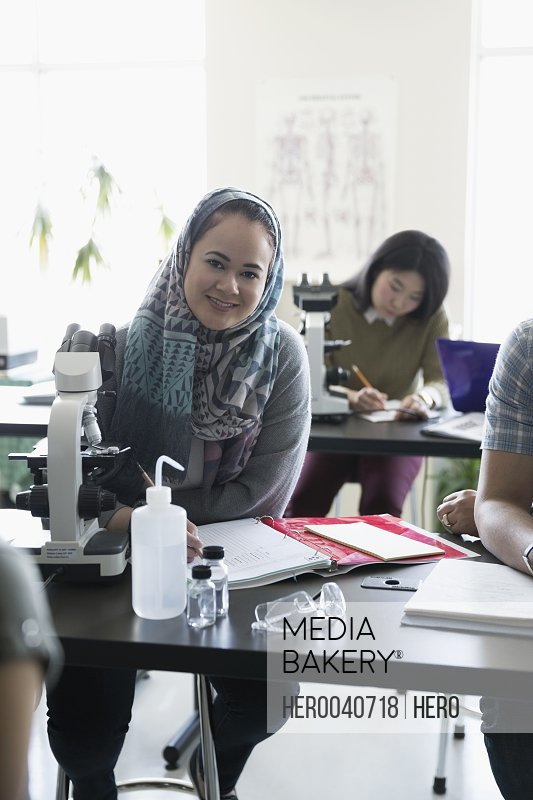 Portrait smiling college student in hijab at microscope in science laboratory