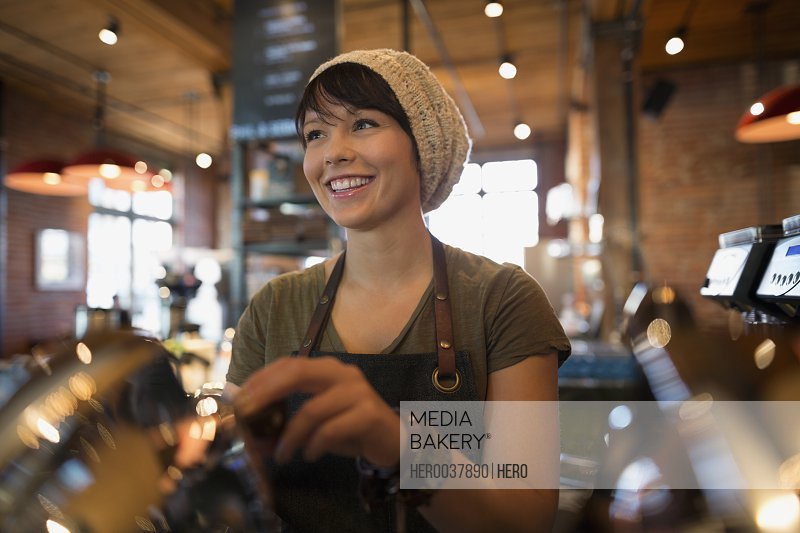 Smiling barista working in coffee shop