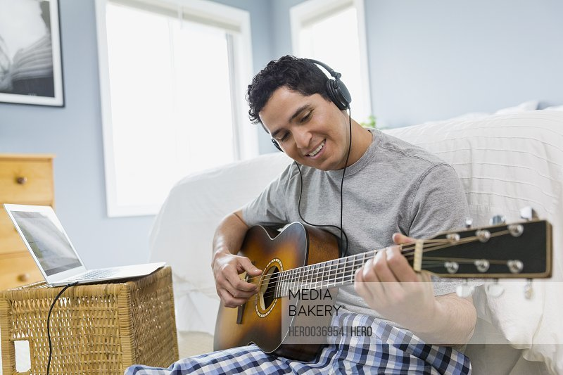 Man playing guitar while listening to music