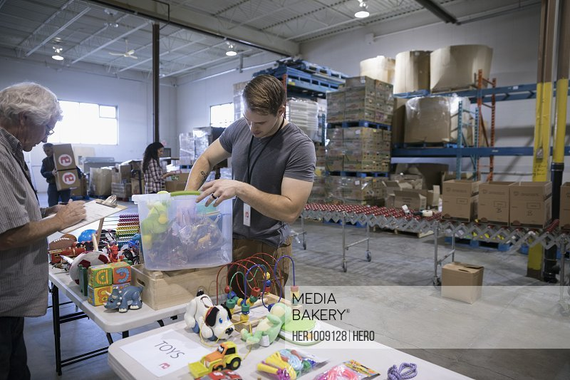 Male volunteers sorting toys for toy drive in warehouse