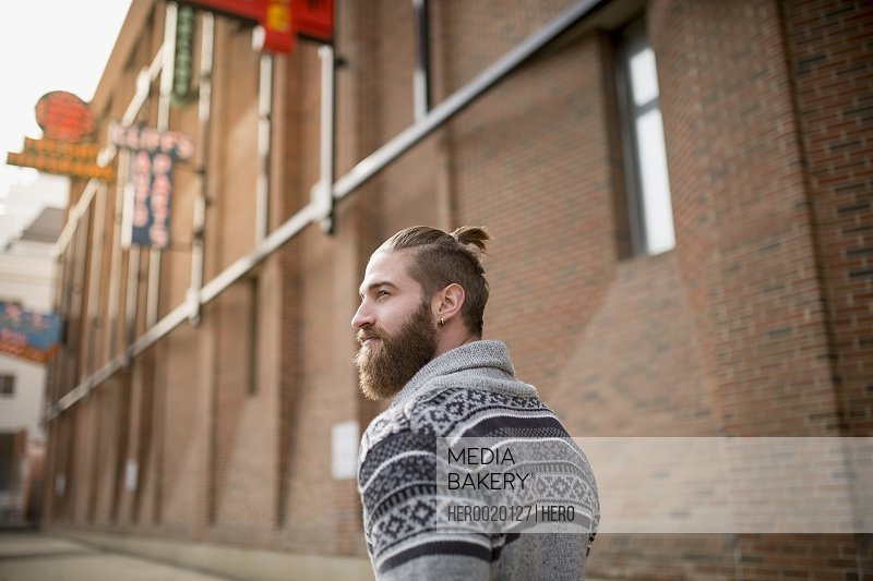 Bearded man in sweater walking down urban street