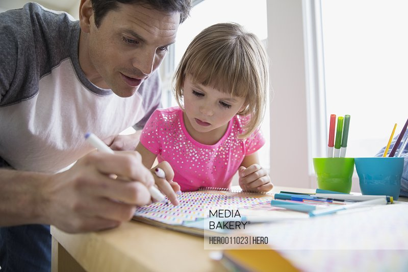 Father and daughter making paper crafts at table