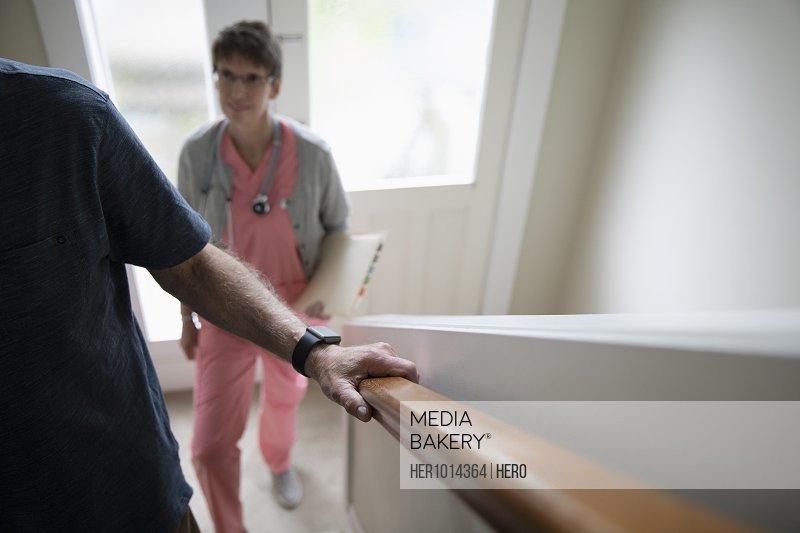 Home caregiver watching senior man climbing stairs