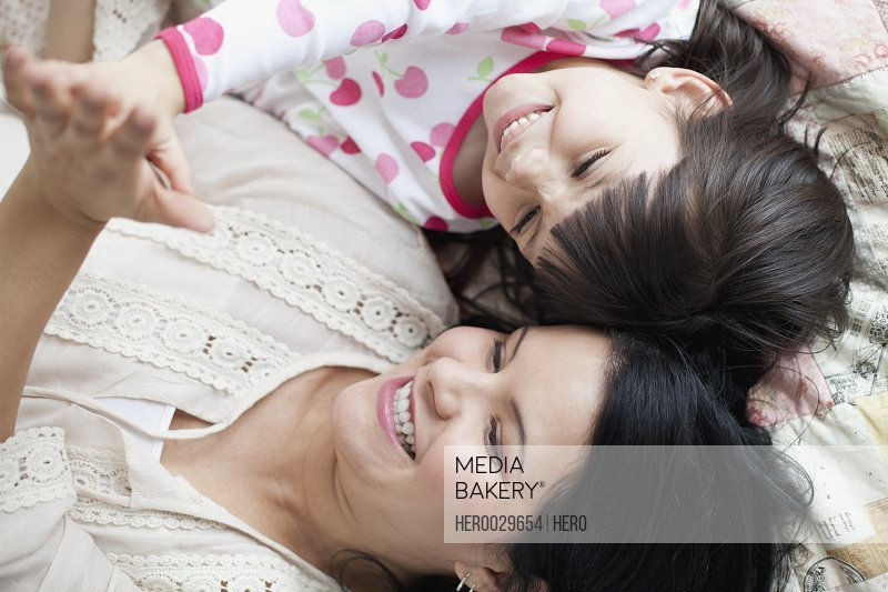mom and young daughter touching hands
