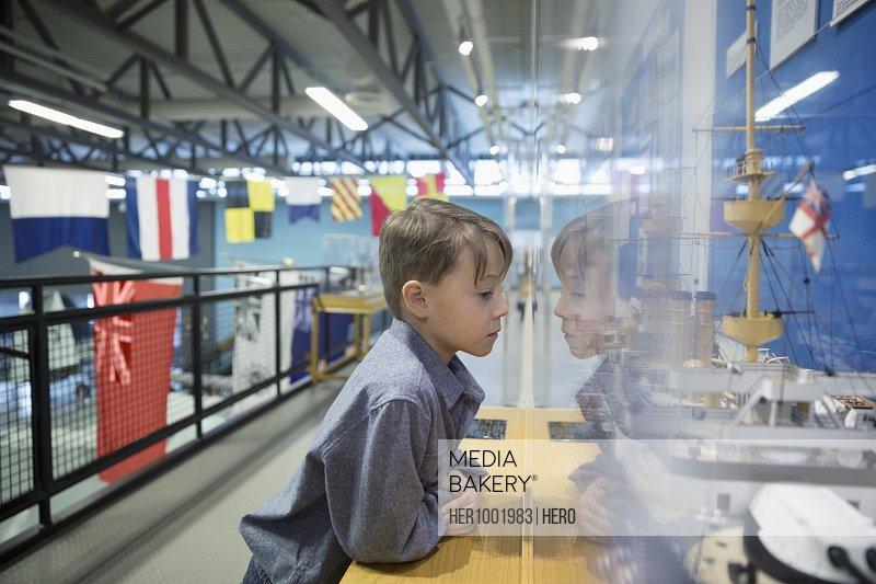 Curious boy viewing Naval ship exhibit in war museum