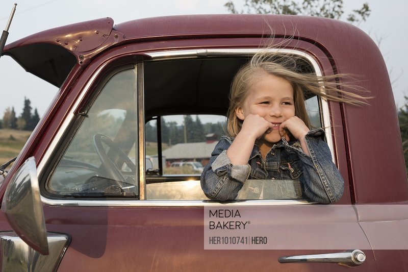 Smiling, carefree blonde girl sitting in truck