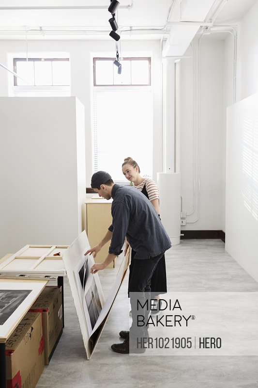 Art gallery owners viewing prints