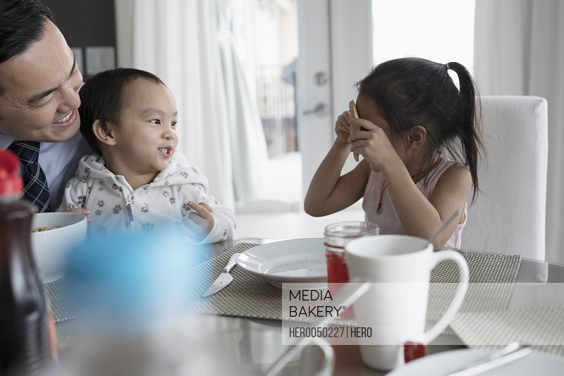 Playful father and children at breakfast table