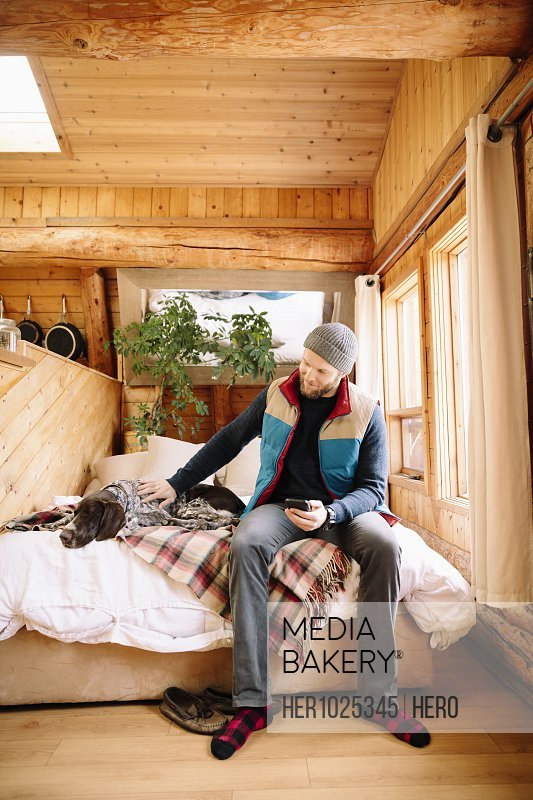 Man with dog on cabin bed