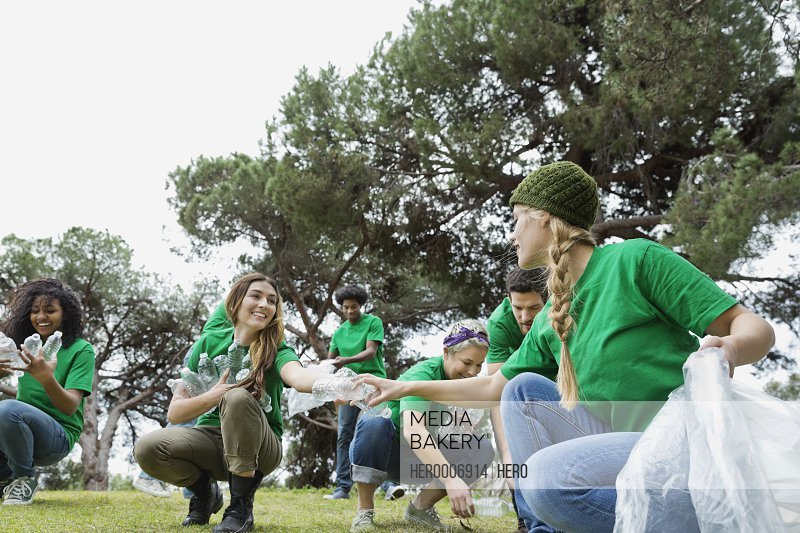 Group of happy environmentalists collecting plastic bottles in park