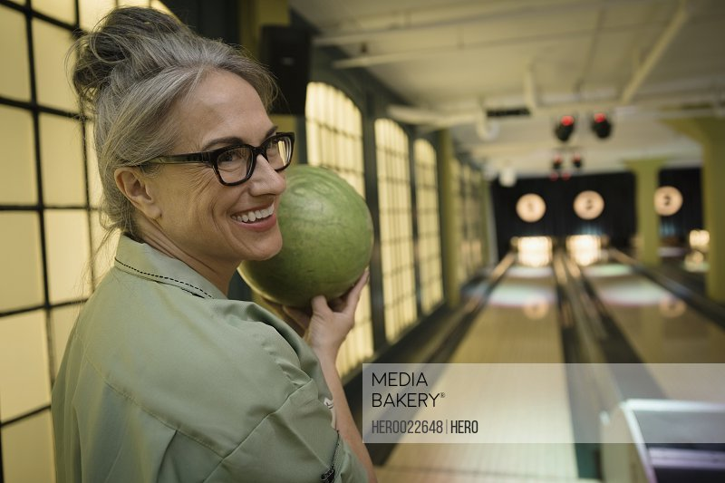 Smiling woman holding bowling ball at bowling alley