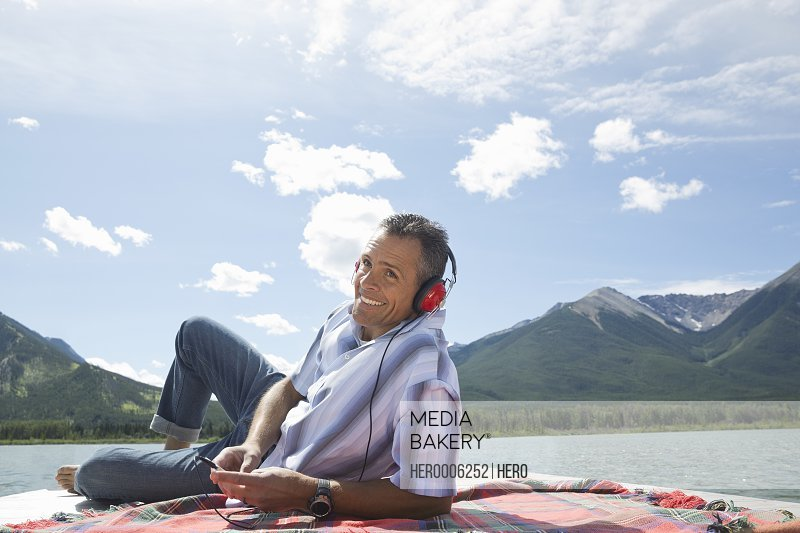 Mature man listening to music on dock