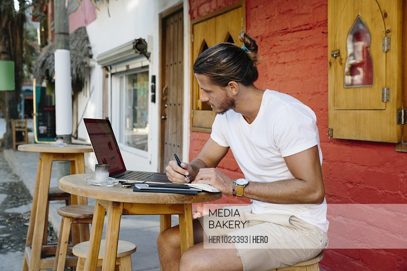 Young male tourist working at laptop at sidewalk cafe, Mexico
