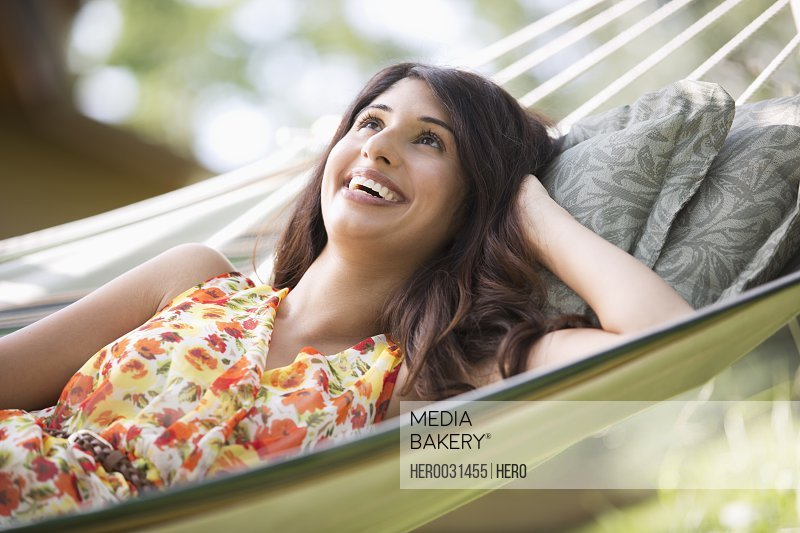 pretty mid-adult woman gazing up while lying on a hammock