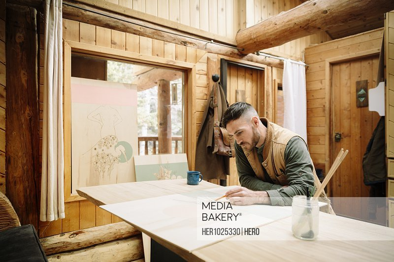 Male artist drawing at cabin table