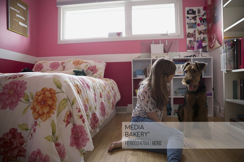 Dog and girl face to face bedroom floor