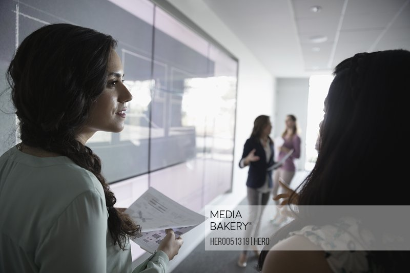 Businesswomen talking in conference room meeting at projection screen