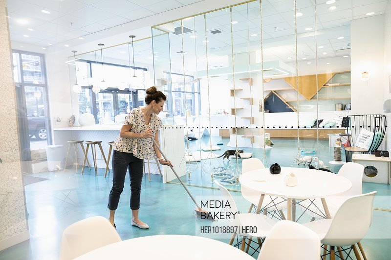 Female business owner sweeping cat cafe