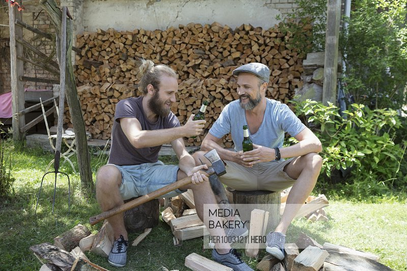 Male friends drinking beer and chopping wood in rural yard