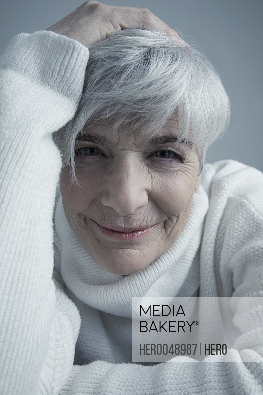 Close up portrait confident Caucasian senior woman with short gray hair and head in hands