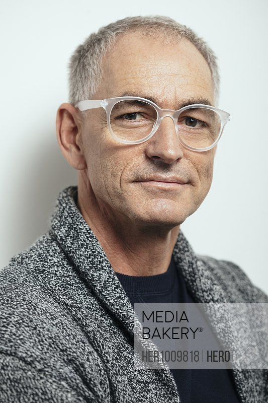 Portrait confident mature man in sweater and eyeglasses