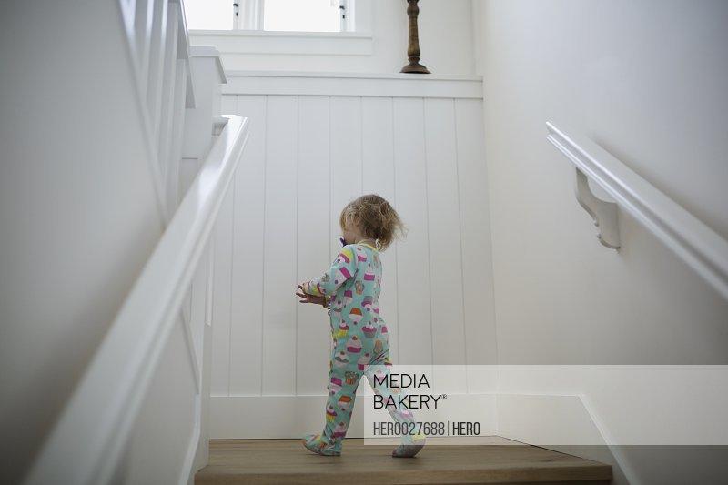 Girl in onesie pajamas on staircase landing