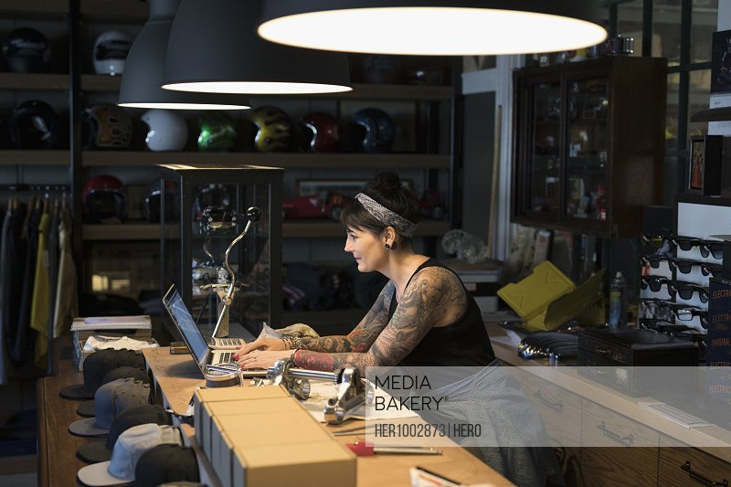 Female motorcycle shop owner working late at laptop behind counter