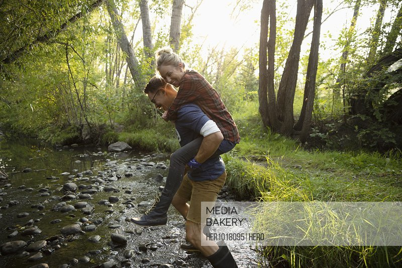 Playful couple piggybacking through stream in woods