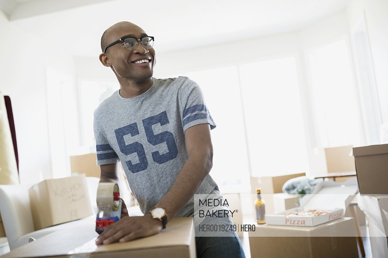 Smiling man taping moving box