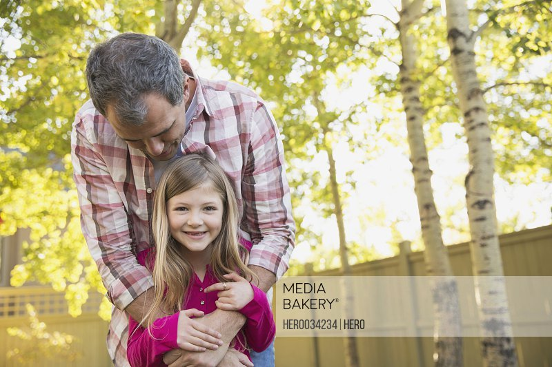 Portrait of happy daughter with father embracing her from behind