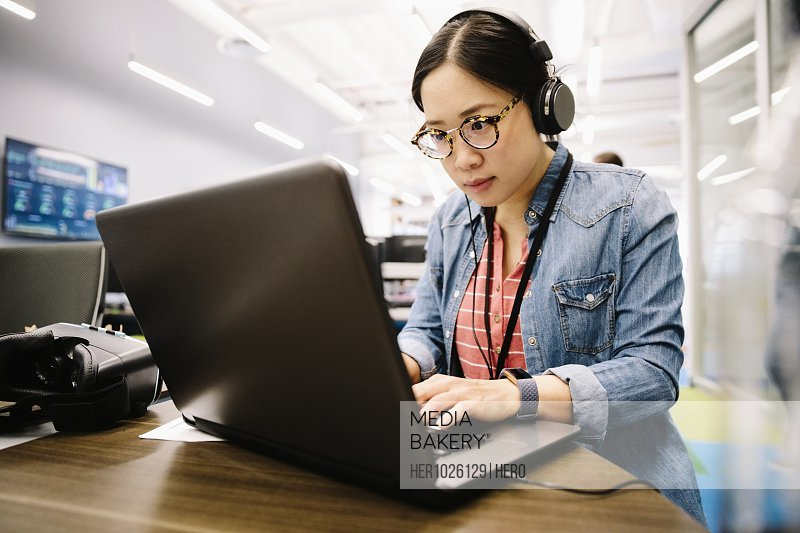 Creative businesswoman with headphones working at laptop in office